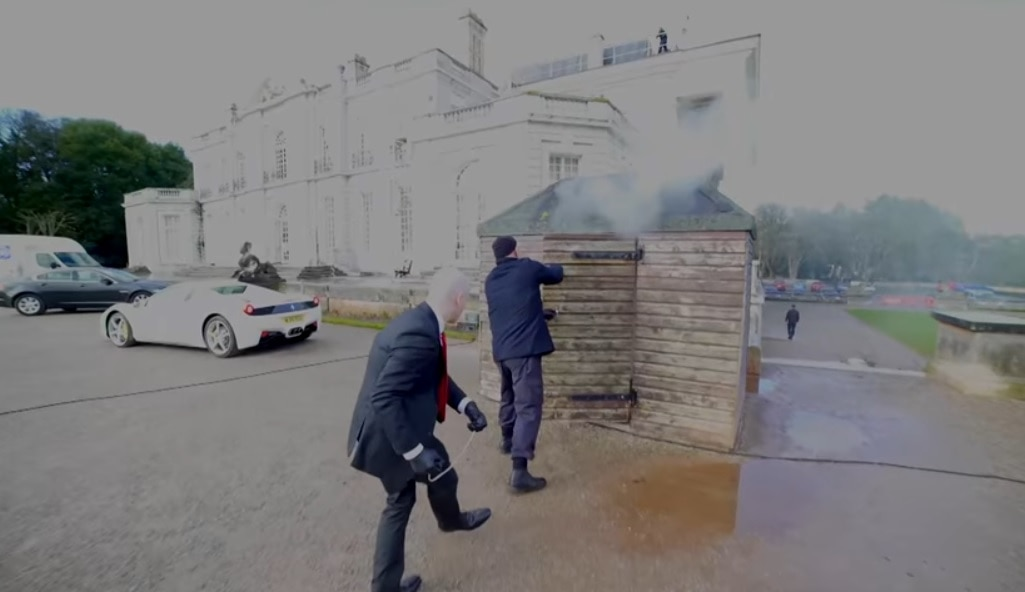 A live action of Hitman, showing Agent 47 in his black suit preparing to assassinate someone by a burning shed.