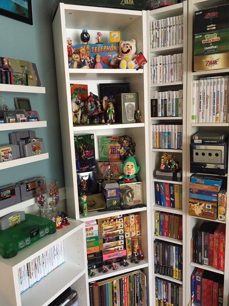 A video game collection neatly organised onto white shelves.