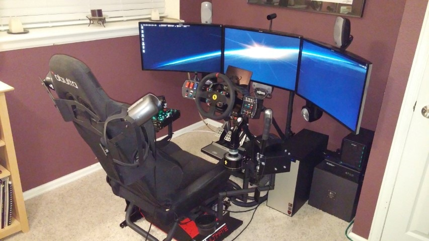A gaming PC set up with a custom-made chasis, steering wheel and 3 screens.