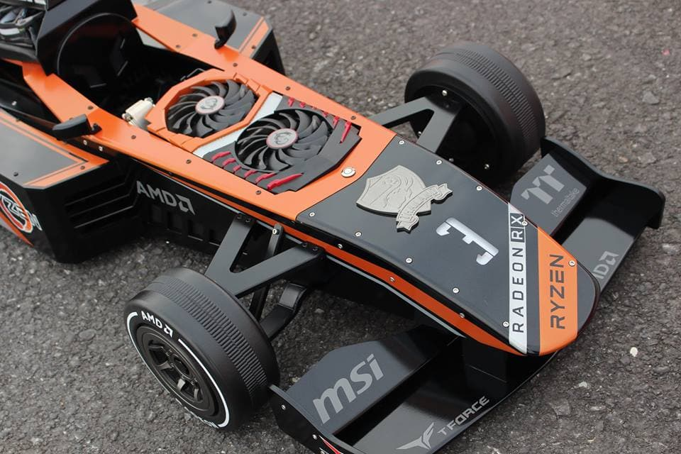 A PC built into a black and orange miniature Formula 1 car.