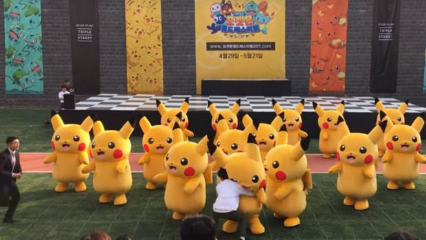 An army of Pikachus, with the middle one being grabbed by someone in white.