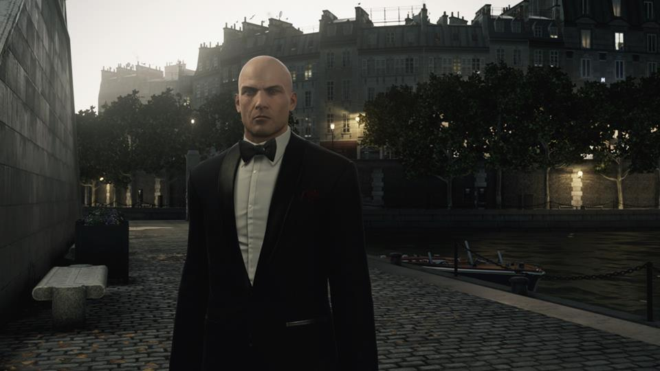 Agent 47 in Hitman wearing a tuxedo in front of a boat and some buildings.