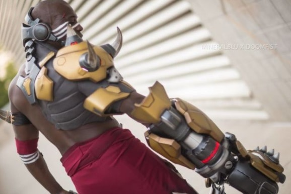Doomfist cosplay looking down at his gold fist.
