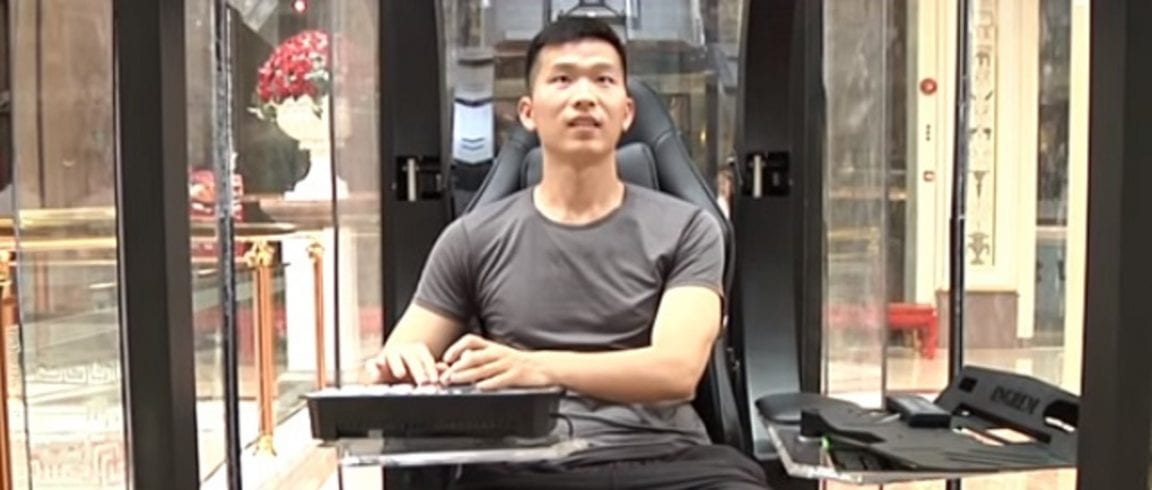 An adult male sitting inside a glass pod playing video games.