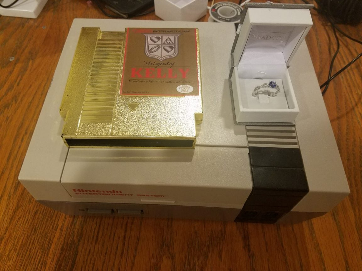 A golden NES game cartridge on a NES console with a ring.