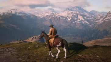A cowboy on a horse looks at a mountain in the distance.