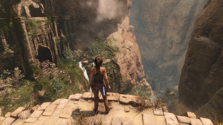 Tomb Raider's Lara Broft looking down at a tomb from a ledge.