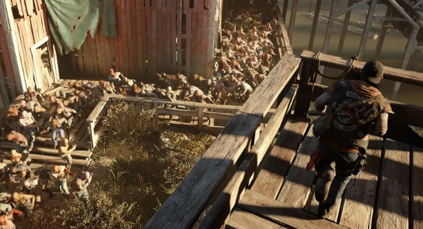 Days Gone showing a man on top of a wooden walkway looking down at a hoard of zombies.