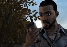 Lee from The Walking Dead game holding a walkie-talkie.