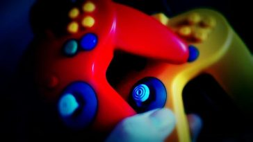 Two N64 controllers, one red and one yellow, being held on top of each other.