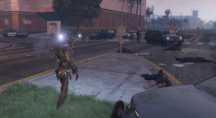Predator, the alien hunter, standing in front of a fleet of police cars in GTA 5.